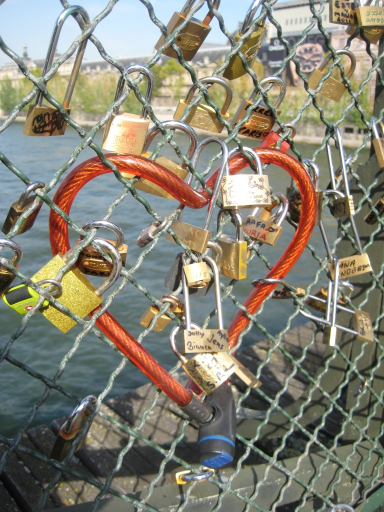 A red bike lock is shaped into a heart and surrounded by other Love Padlocks on the Pont D'Arts bridge in Paris, France