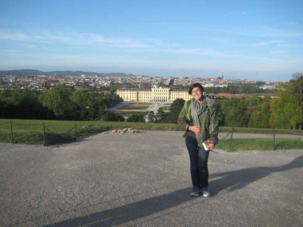 Karra standing atop the Gloriette in Vienna Austria with Schonbrunn Palace in the background