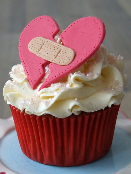 Red cupcake with whipped cream and a fondant pink broken heart. A fondant bandage is placed over the break in the middle of the heart.