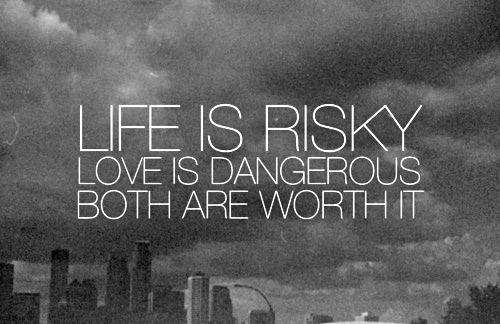 "White text over a grey background of a cityscape. Text says ""Life is Risky. Love is Dangerous. Both are Worth It."""