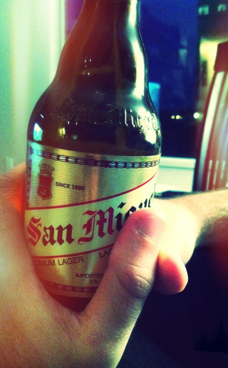 Someone holding a bottle of San Miguel beer