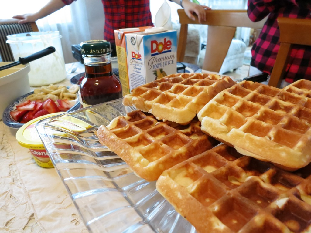 Waffles on a plate with juice, maple syrup, and fruit in the background