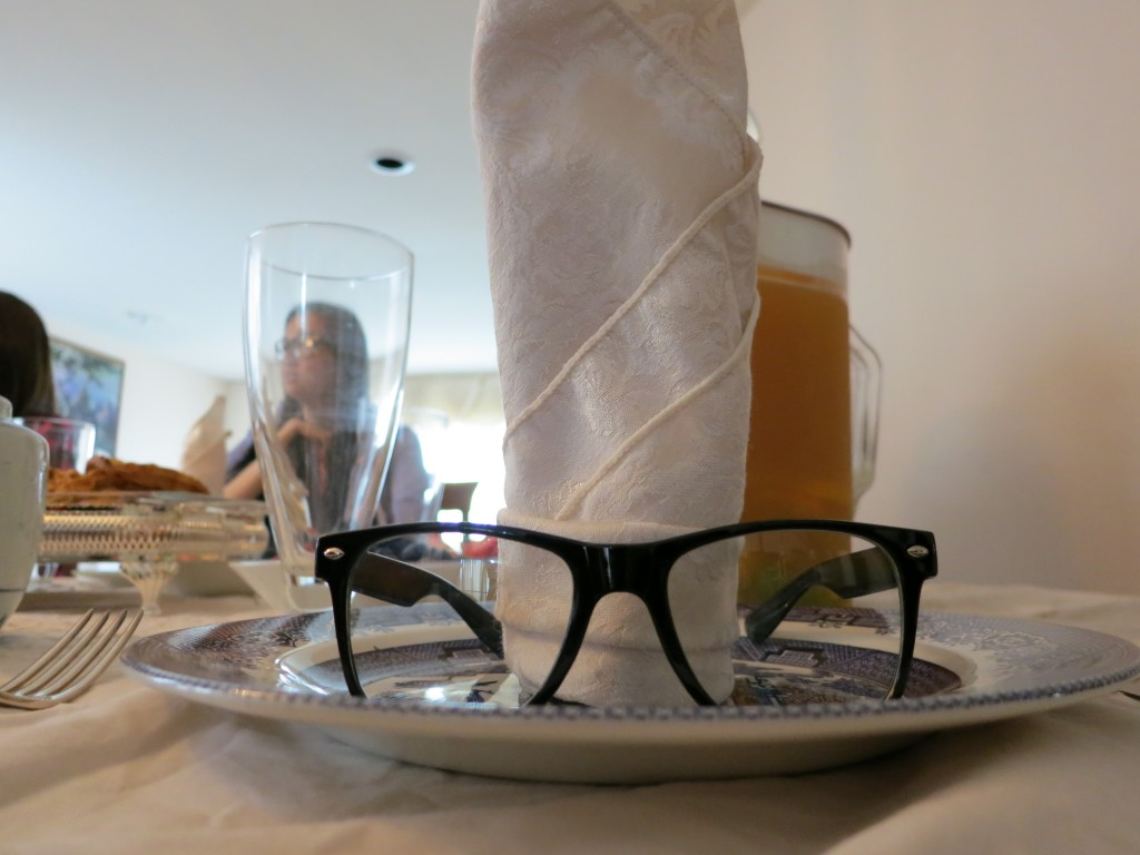 Thick black frame glasses on a plate with tall napkin in the background