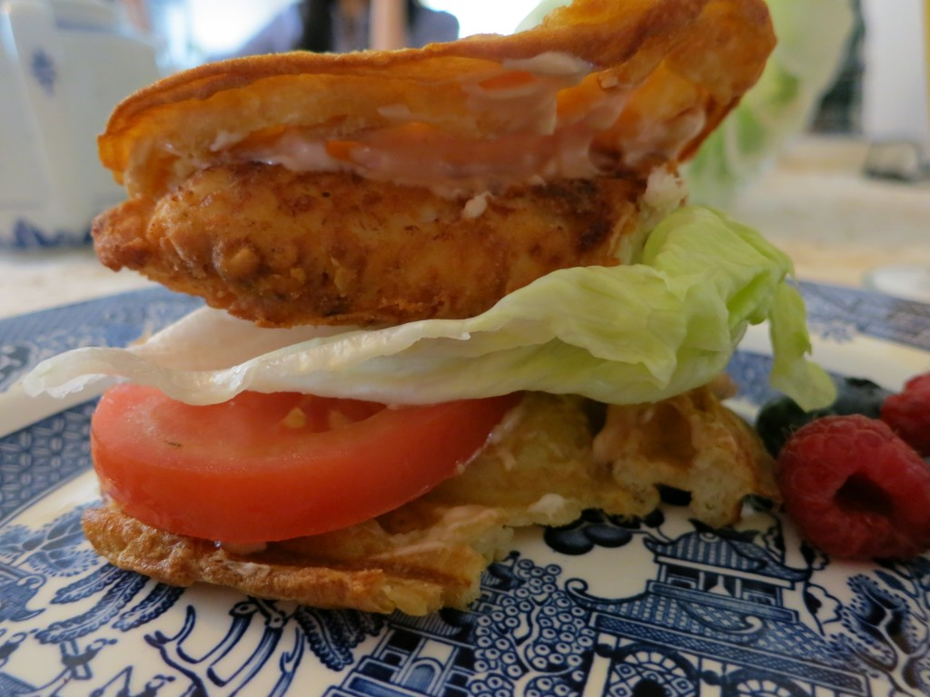 Picture of two waffle pieces with fried chicken, thousand island dressing, lettuce and tomato in the middle.