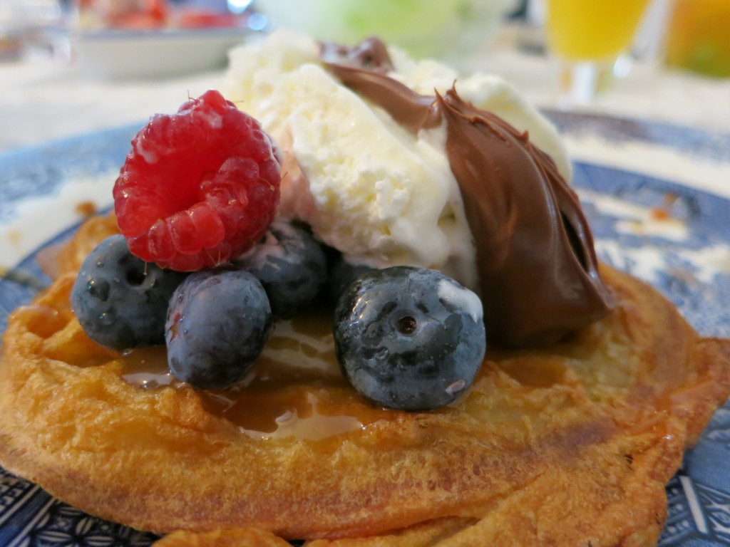 Waffle with blueberries, raspberries, caramel syrup, ice cream, and Nutella on top