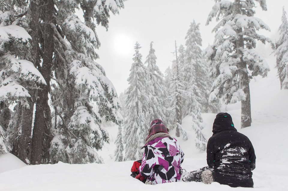 Karra and her friend sitting on Grouse Mountain admiring the view