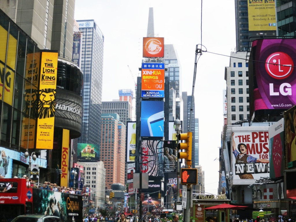 Daytime image of Times Square in New York CIty with billboards for Lion King, ads for Chinese Company, etc