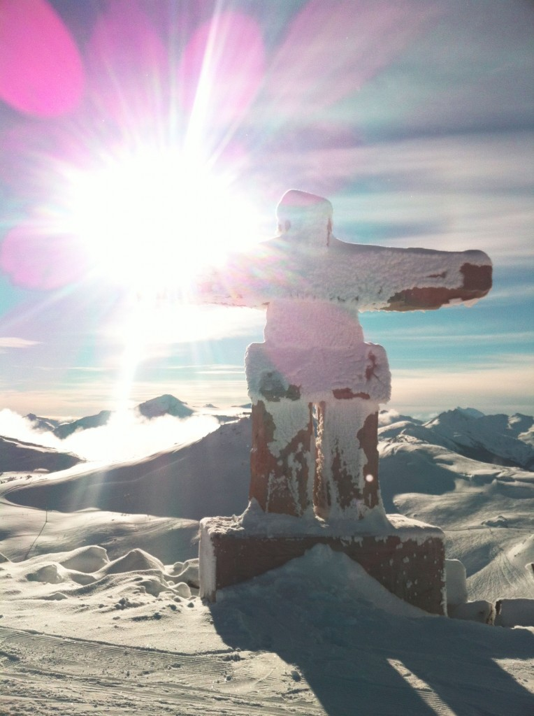 Sun shining on a snow-covered inukshuk in Whistler, BC